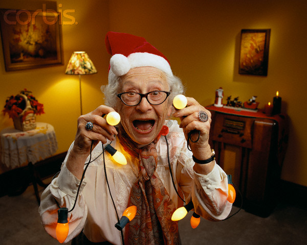 Happy Senior Woman Wearing Christmas Lights --- Image by © Don Mason/CORBIS
